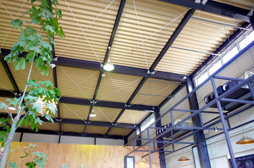 SIENA COFFEE FACTORYの高い天井と緑とソファ
